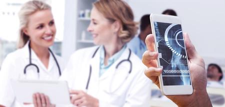 doctoras: mano que sostiene tel�fono inteligente contra los m�dicos sonrientes hablando el uno al otro