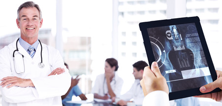 Man using tablet pc against doctor with group around table in background at hospital photo
