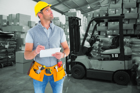 Manual worker looking away while writing on clipboard against warehouse worker loading up pallet