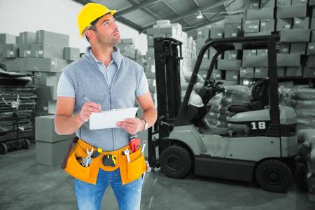 Ouvrier regardant loin en écrivant sur presse-papiers contre les travailleurs de l'entrepôt de chargement jusqu'à palette