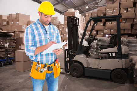 Manual worker writing on clipboard against warehouse worker loading up pallet
