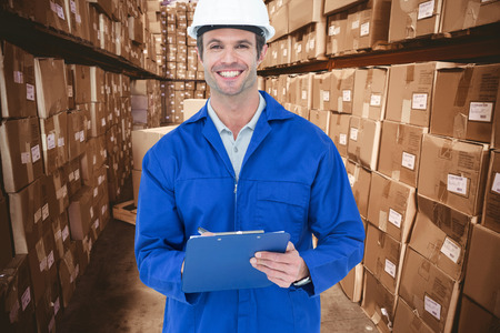 supervisor: Confident supervisor writing notes against boxes in warehouse Stock Photo