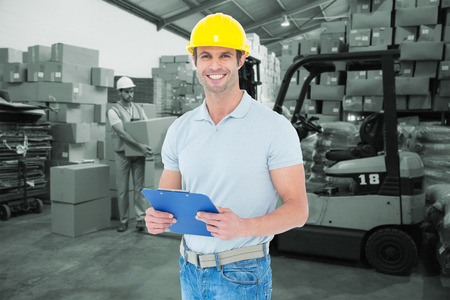Happy architect holding clip board against warehouse worker loading up pallet photo
