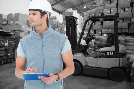 Architect writing on clip board against warehouse worker loading up pallet photo