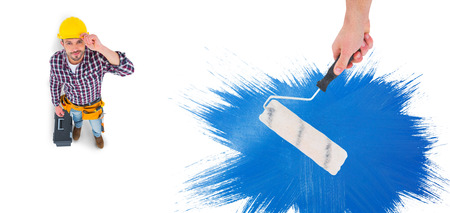 paint roller: Handyman holding paint roller  against blue paint