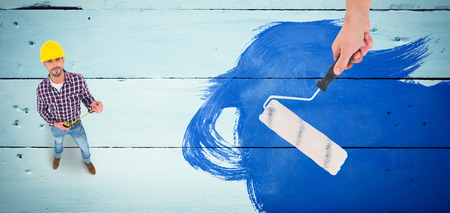 Handyman holding paint roller  against painted blue wooden planks photo