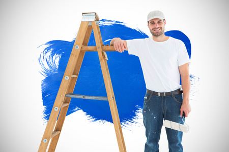 redecorating: Happy man with paint roller standing by ladder against blue paint