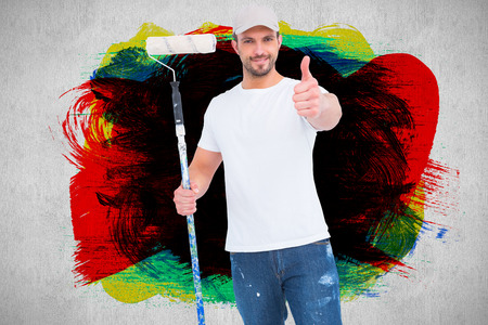 Handyman holding paint roller  against white and grey background photo