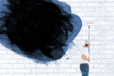 Man using paint roller on white background against white wall photo