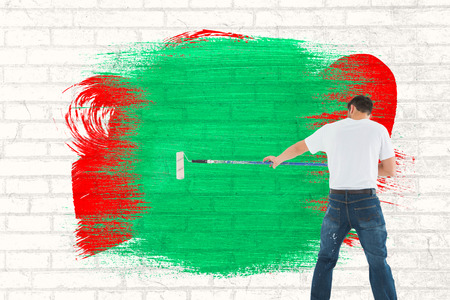 legs crossed at knee: Man using paint roller on white background against white wall