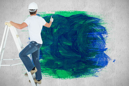 Man on ladder painting with roller against white and grey background photo