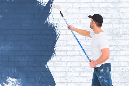 Handyman painting with roller  against white wall