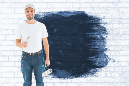 legs crossed at knee: Happy man holding paint roller and paintbrush against white wall