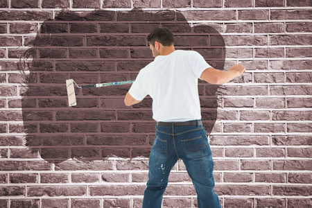 legs crossed at knee: Man using paint roller on white background against red brick wall