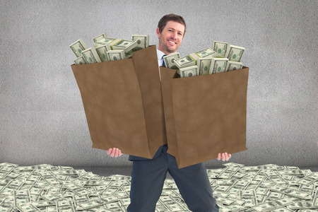 paper money: Businessman carrying bag of dollars against grey room Stock Photo
