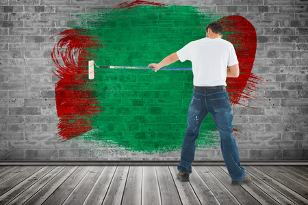 redecorating: Man using paint roller on white background against grey room Stock Photo