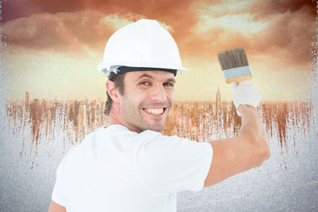 redecorating: Portrait of happy man using paintbrush against sun shining over city