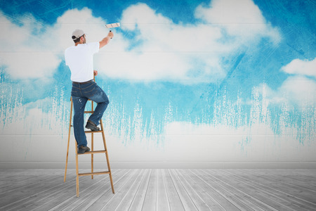 escaleras: Hombre en escalera pintura con el rodillo contra el cielo pintado Foto de archivo