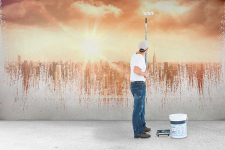 redecorating: Man using paint roller on white background against sun shining over city