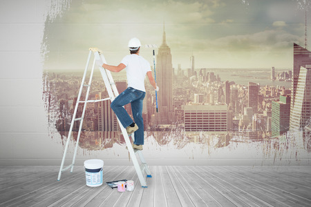 step ladder: Man on ladder painting with roller against room with large window looking on city Stock Photo