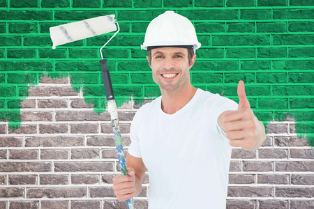 red paint roller: Man holding paint roller while gesturing thumbs up against red brick wall Stock Photo