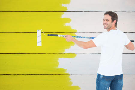 redecorating: Happy man using paint roller against painted blue wooden planks