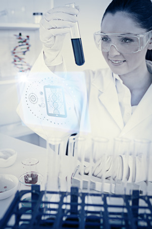 Science and medical graphic against attractive redhaired woman holding a test tube