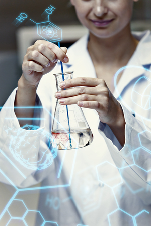 erlenmeyer: Science and medical graphic against portrait of a female scientist shaking liquid in an erlenmeyer Stock Photo