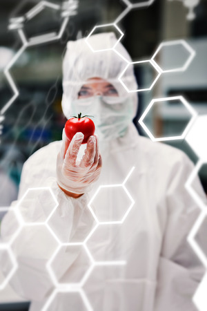 protective suit: Science and medical graphic against woman wearing protective suit holding a tomato Stock Photo