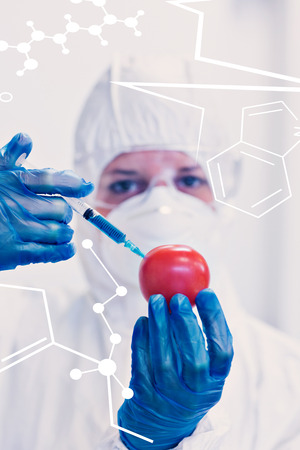Science and medical graphic against researcher in protective suit injecting tomato at lab photo