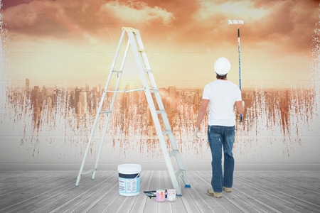 Man with paint roller standing by ladder against sun shining over city