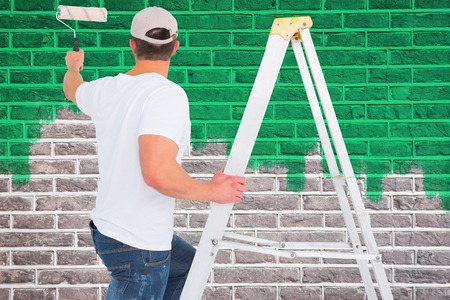 climbing ladder: Handyman climbing ladder while using paint roller against red brick wall