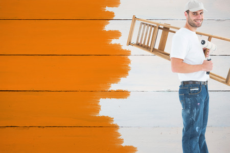 step ladder: Man with paint roller and step ladder against painted blue wooden planks Stock Photo
