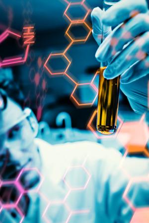 biotecnologia: Retrato de un científico masculino mirando un tubo de ensayo contra la ciencia y gráfica médica Foto de archivo