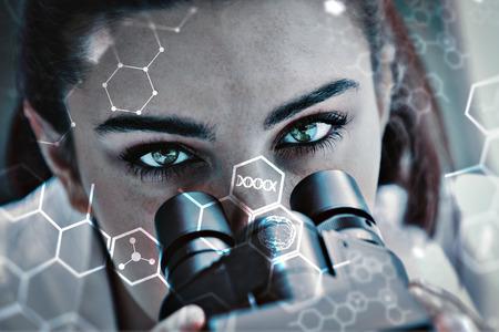 Close-up van een wetenschapper die met een microscoop tegen de wetenschap en medische grafische