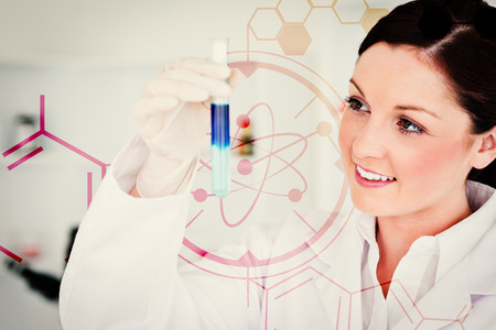 Science and medical graphic against smiling redhaired scientist looking at the camera while holding a test tube