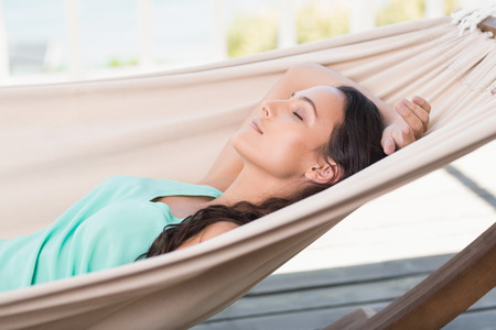 escapism: Pretty brunette relaxing on a hammock in patio Stock Photo