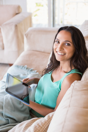 Pretty brunette using tablet pc on the couch at home in the living room Stok Fotoğraf