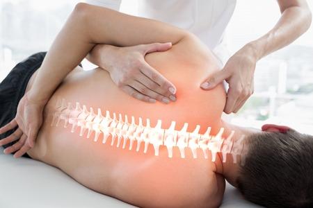 massage homme: Composite numérique des os en surbrillance de l'homme à la physiothérapie Banque d'images