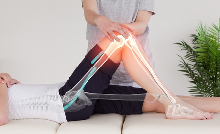 muscle retraining: Digital composite of Highlighted bones of woman at physiotherapist Stock Photo