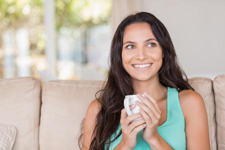 mujer tomando cafe: Pretty morena sosteniendo su taza en casa en la sala de estar Foto de archivo