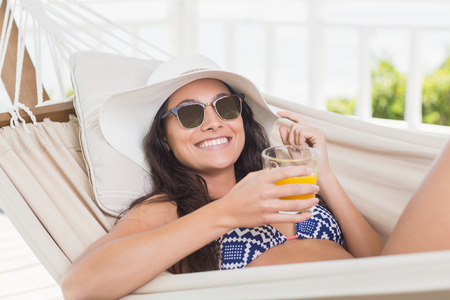 Pretty brunette relaxing on a hammock and drinking orange juice in patio photo