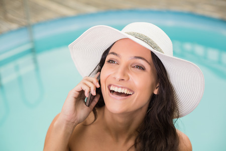 Beautiful woman in bikini relaxing by swimming pool photo