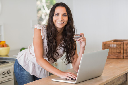 electronic card: Pretty brunette shopping online with laptop in the kitchen