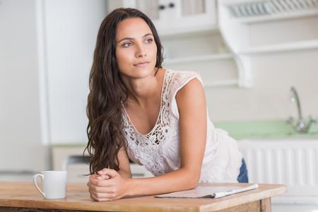 mujer reflexionando: Pensativo guapa morena en la cocina Foto de archivo