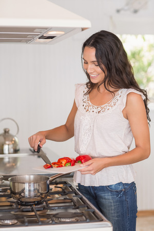 gorgeous woman: Beautiful brunette cooking in the kitchen Stock Photo