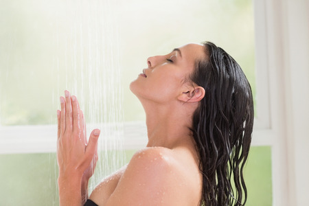 wetting: Pretty brunette taking a shower in a bathroom Stock Photo