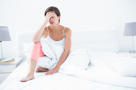pounding head: Beautiful woman suffering from headache at home in the bedroom Stock Photo