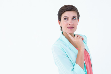 cheek to cheek: Thoughtful brunette with finger on cheek on white background