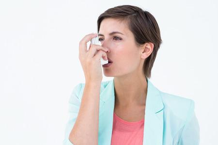 Pretty woman using her inhaler on white background